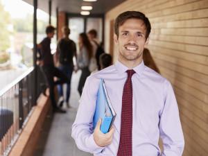 Portrait Of Teacher Standing Outside School Building